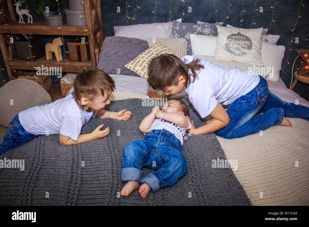 three brothers are lying on the bed. brotherly love big family, many children - Stock Image