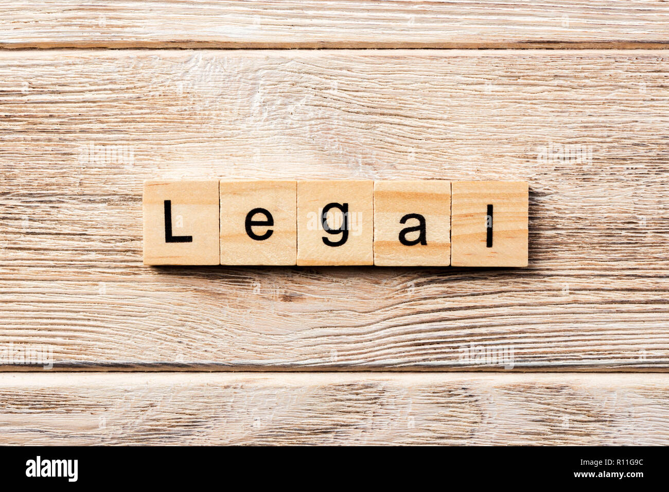 legal word written on wood block. legal text on table, concept. - Stock Image
