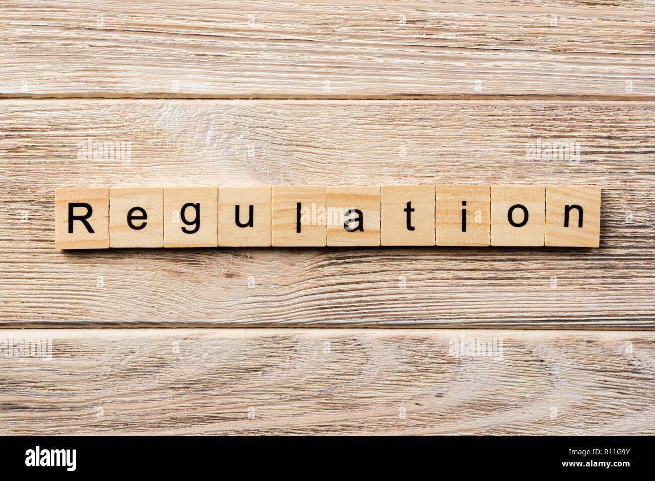regulation word written on wood block. regulation text on table, concept. - Stock Image
