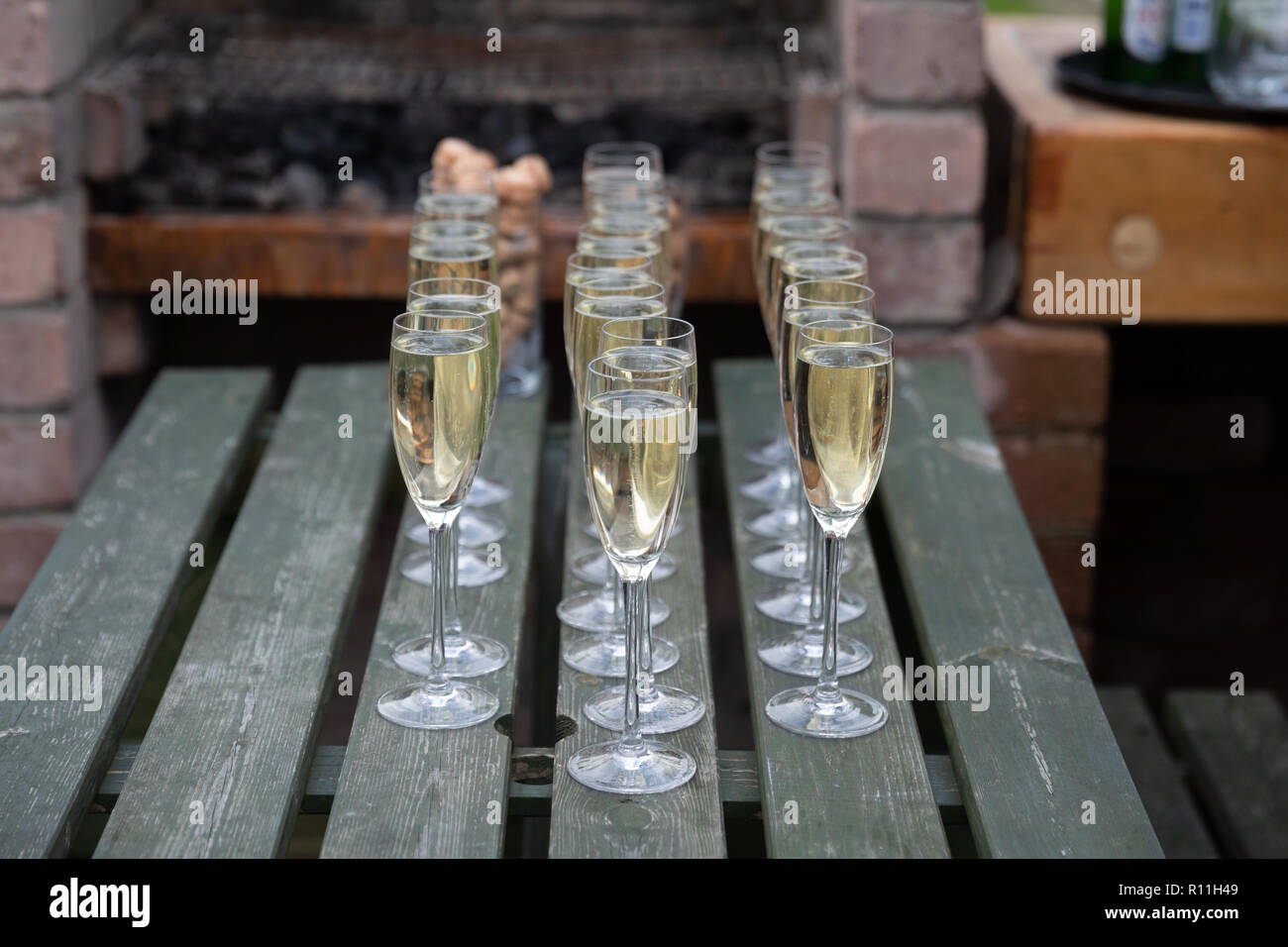 Three lines of champagne in glasses on a picnic table - Stock Image