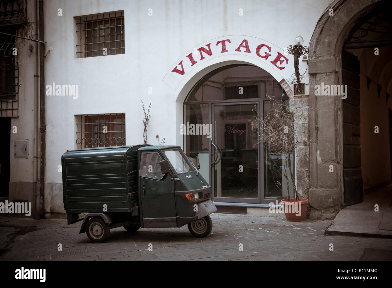 A miniscule Piaggio Ape 50 delivery truck packed in the back streets of Lucca, Italy. - Stock Image
