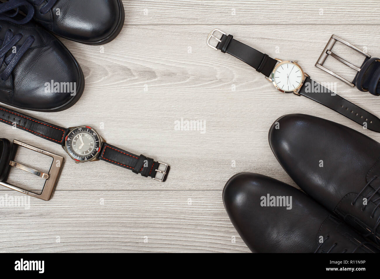 Two pairs of black leather men's shoes, two belts for men and two wristwatches on gray wooden background. Men's accessories. Top view - Stock Image