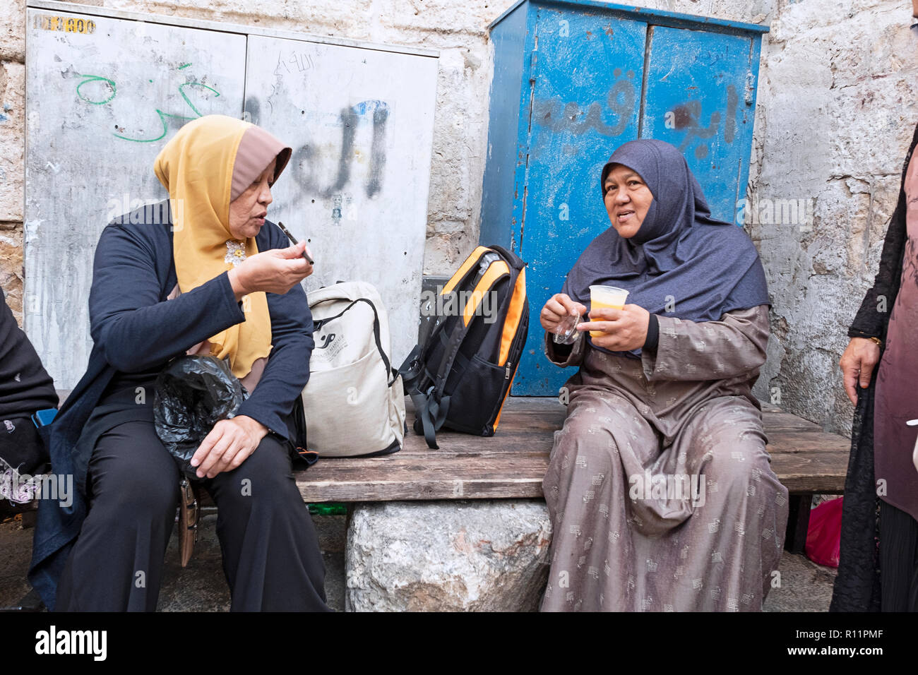 Muslim women in the Old City of Jerusalem, one with a drink and the other with a cigar. - Stock Image