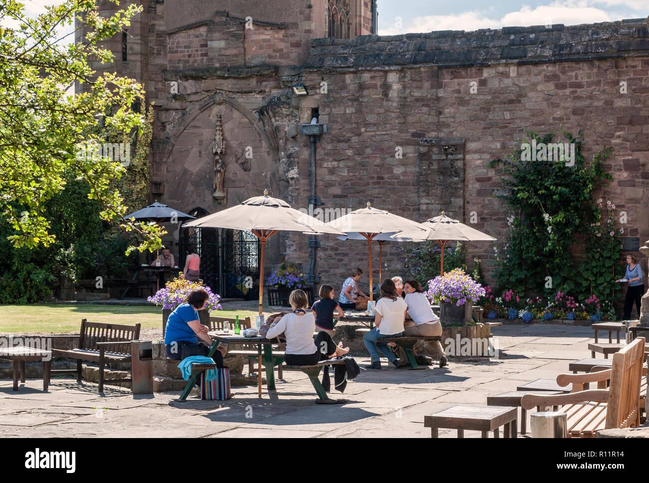 Hereford Cathedral, UK. Visitors relaxing in the Chapter House Garden, next to the Cathedral Cafe - Stock Image