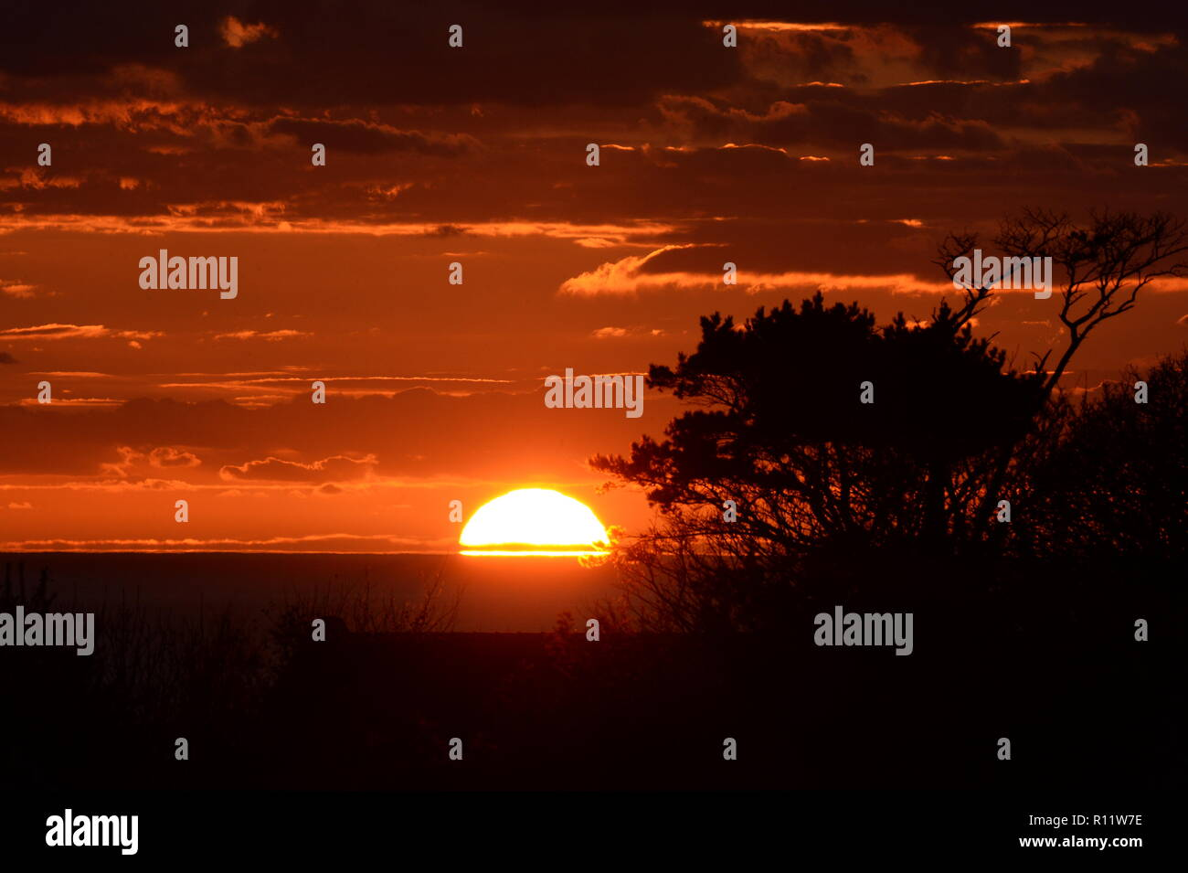 Sunset at Mumbles. A Setting Sun disappears below the horizon causing atmospheric refraction creating the beautiful spectrum of colours in the sky. - Stock Image