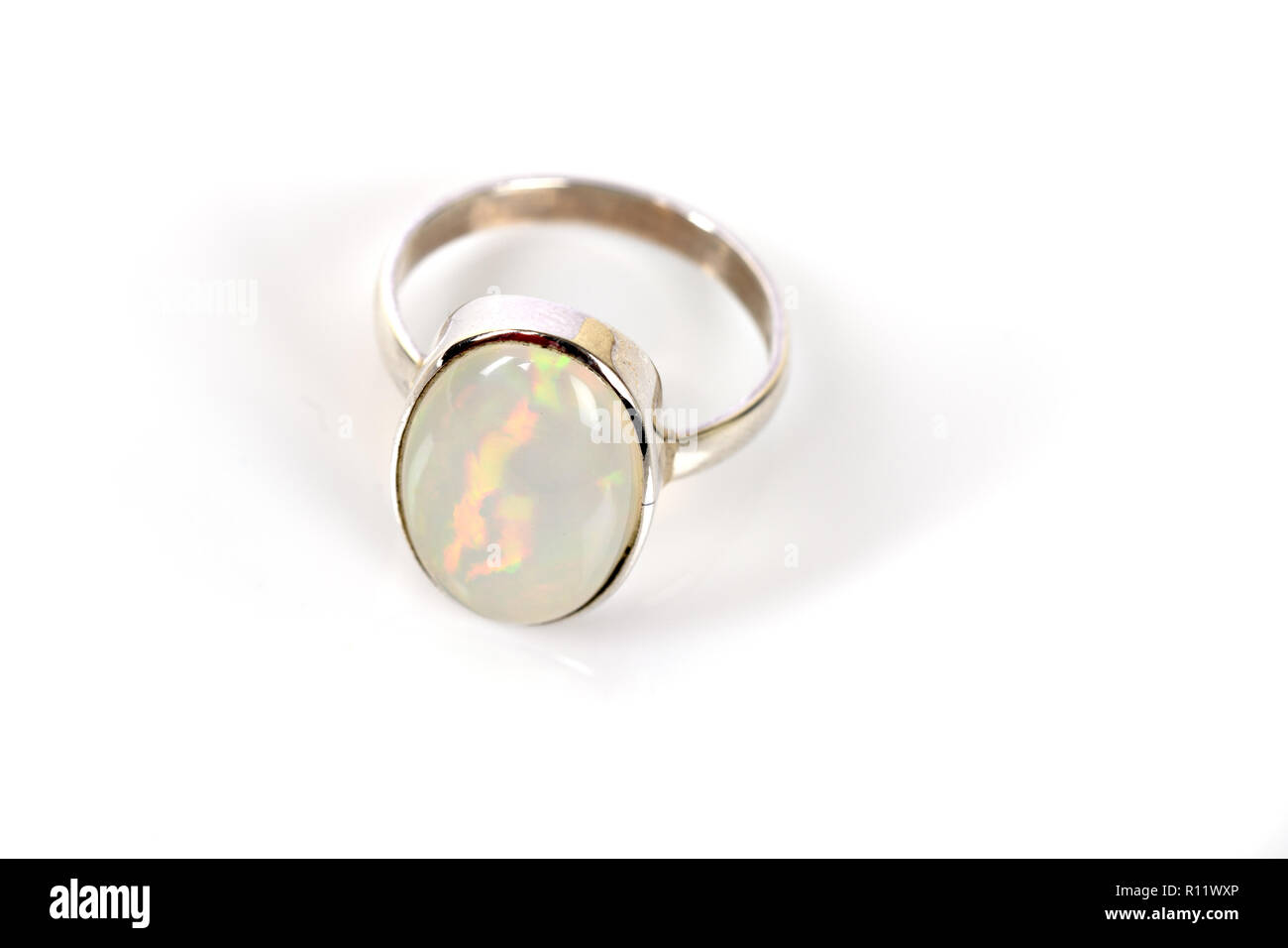 Opal Ring in silver iridescent on white background - Stock Image