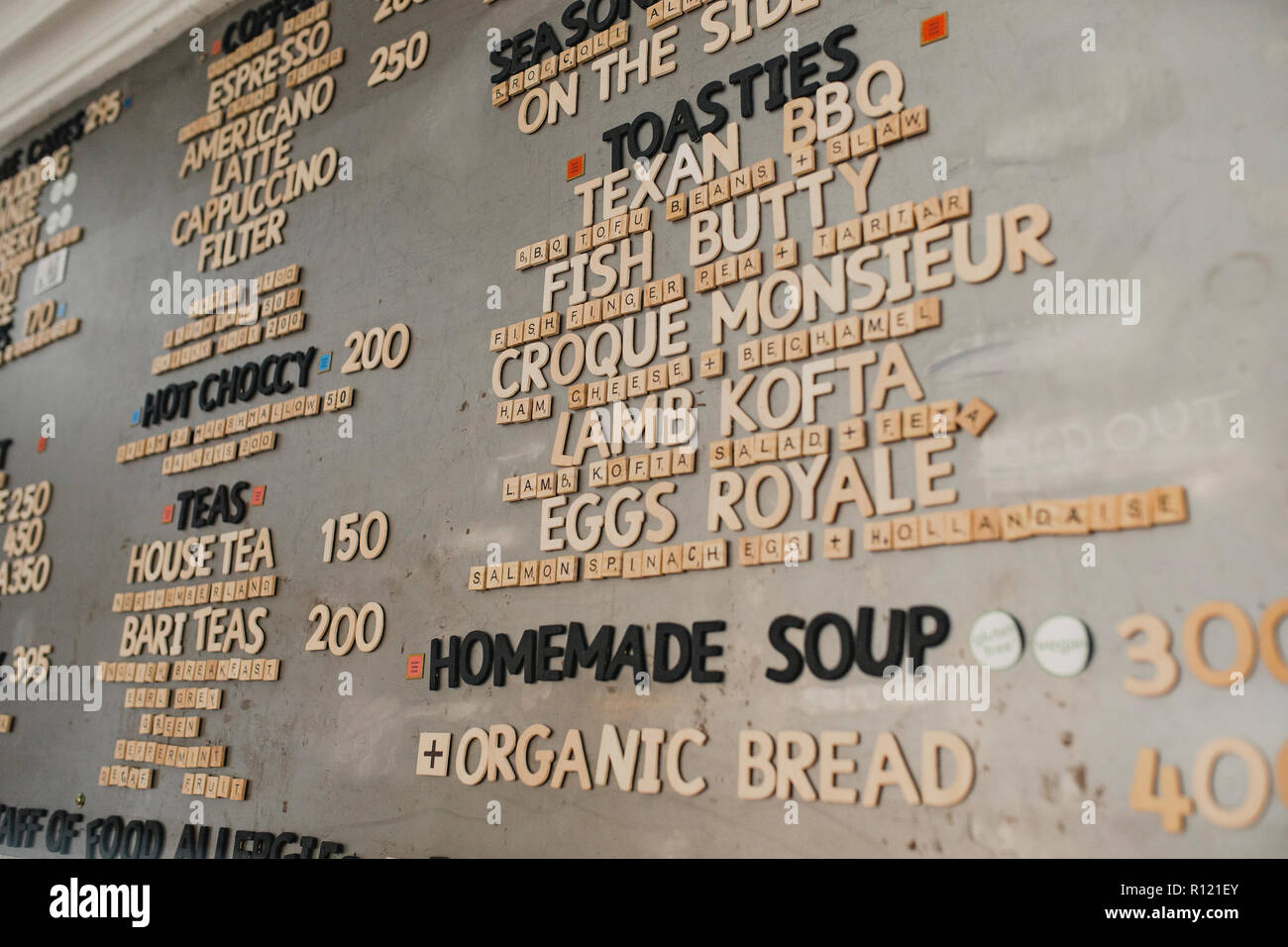 Low Angle View Of A Food Menu On The Wall In A Cafe They Have Used Little Tile Letters On The Wall To Spell Out The Different Items On The Menu Stock