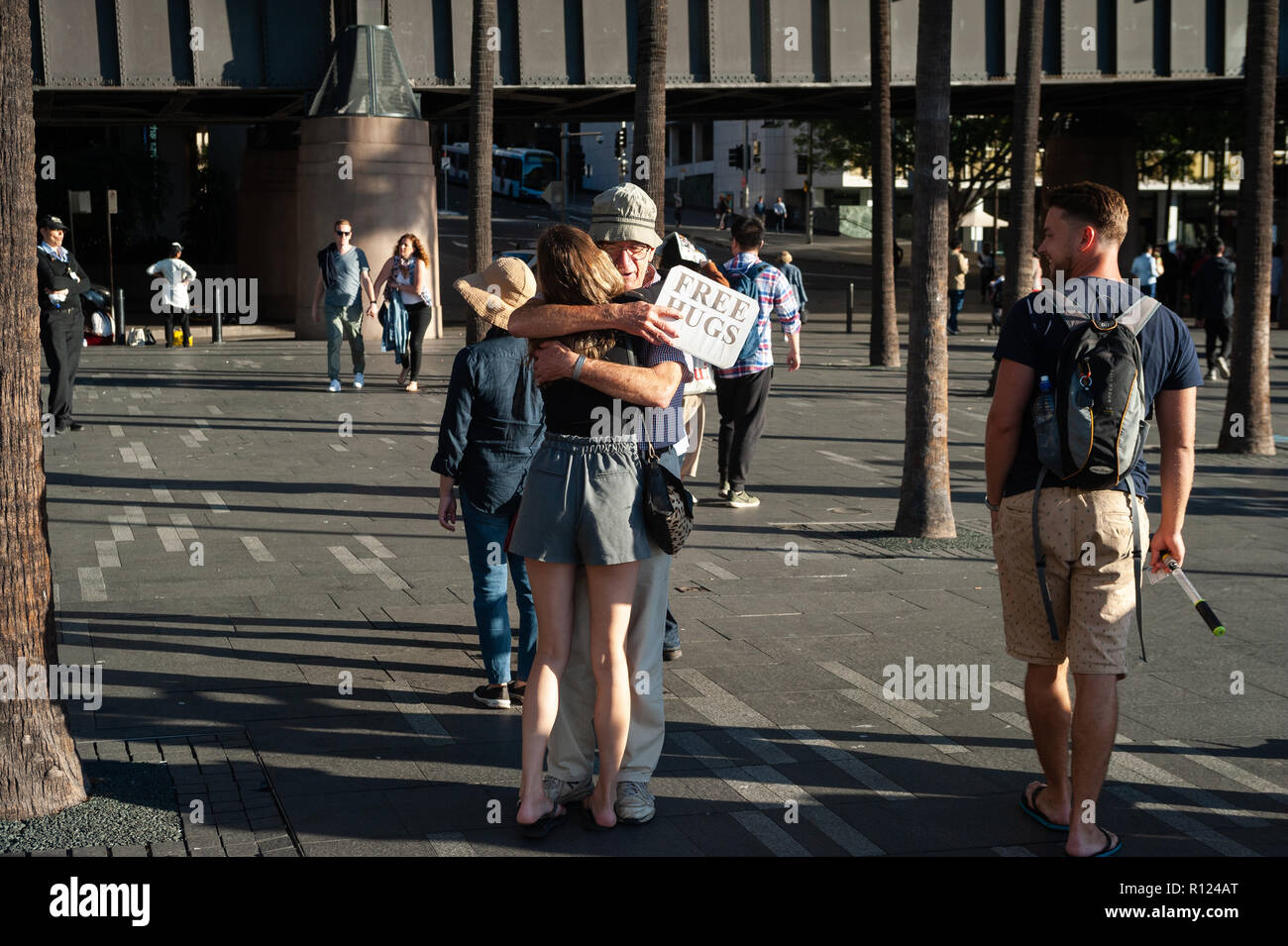 06.05.2018, Sydney, New South Wales, Australia - A man offering free hugs along Circular Quay is hugging a young woman. - Stock Image