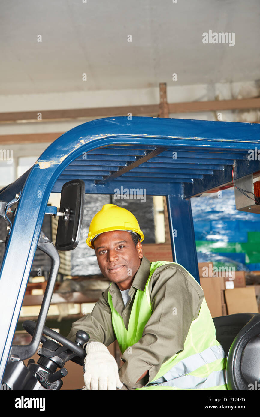 African man on the forklift works as a driver in the warehouse Stock Photo
