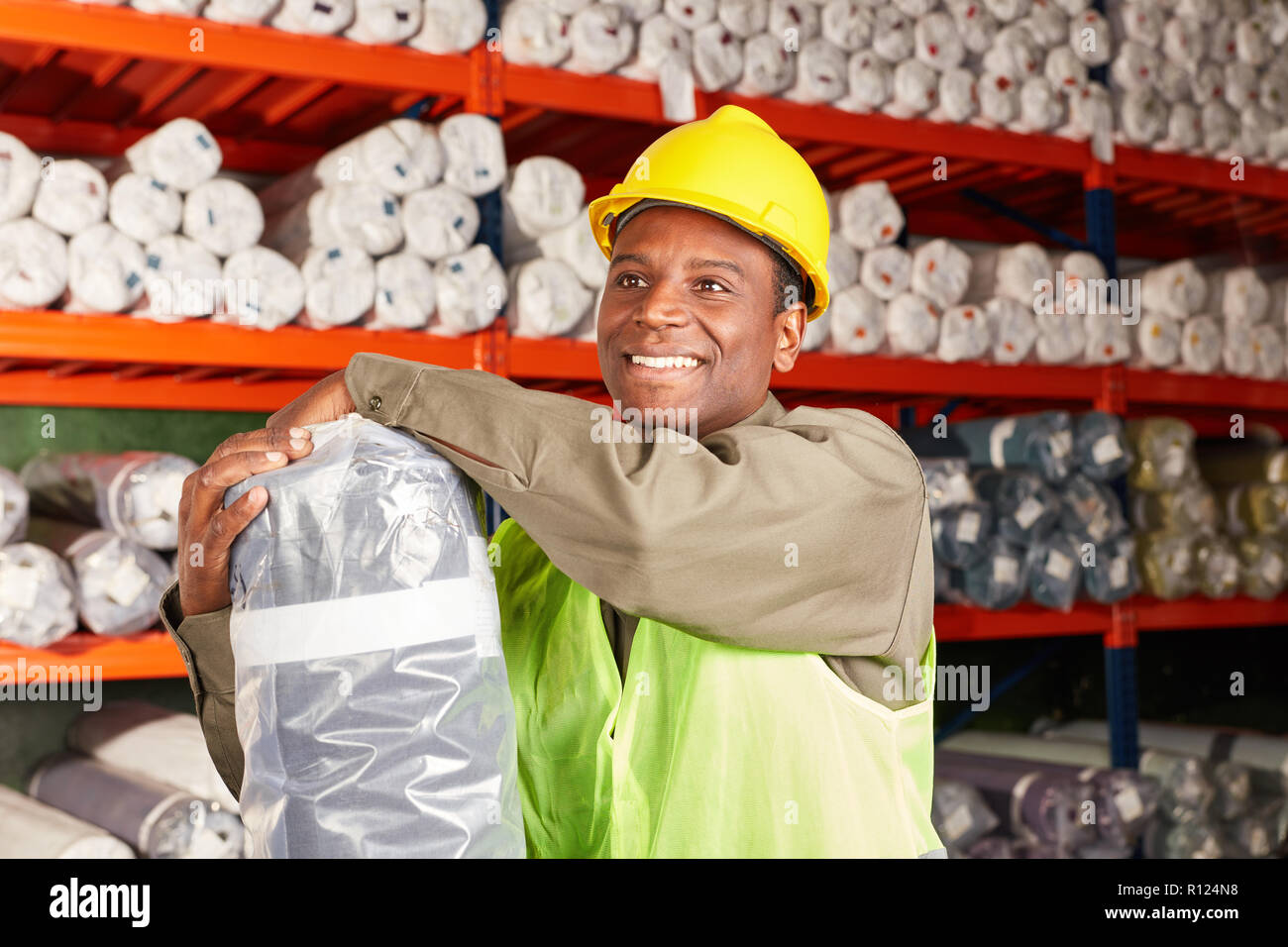 Young man as a logistics apprentice in training with delivery in the carpet warehouse - Stock Image