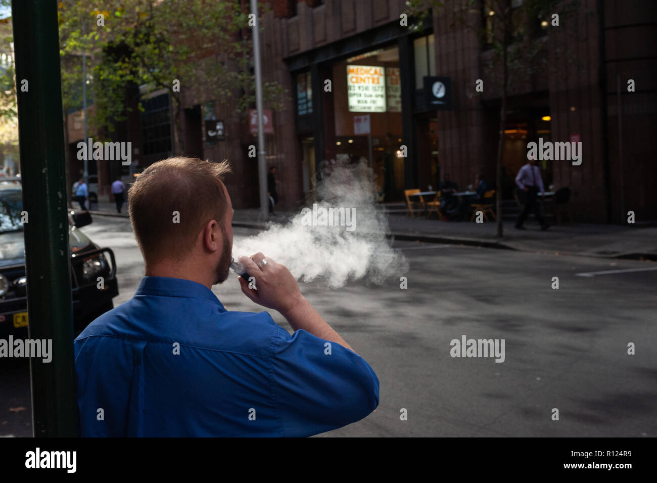 10.05.2018, Sydney, New South Wales, Australia - A man is smoking an electronic cigarette / e-cigarette on a street in Sydney's business district. - Stock Image