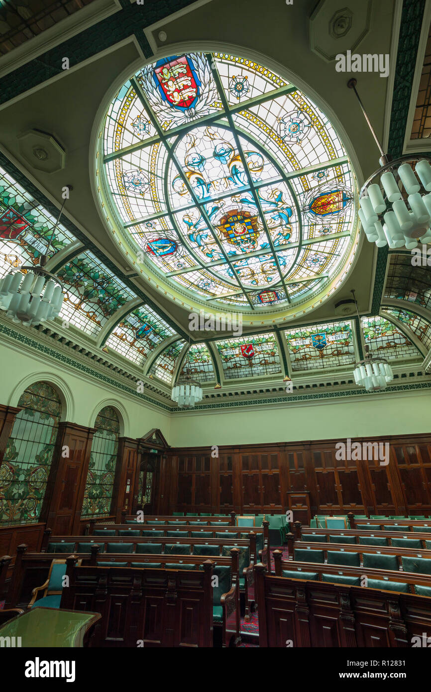 The stained glass ceiling of the council chamber in Halifax Town Hall featuring the town's old coat of arms - Stock Image