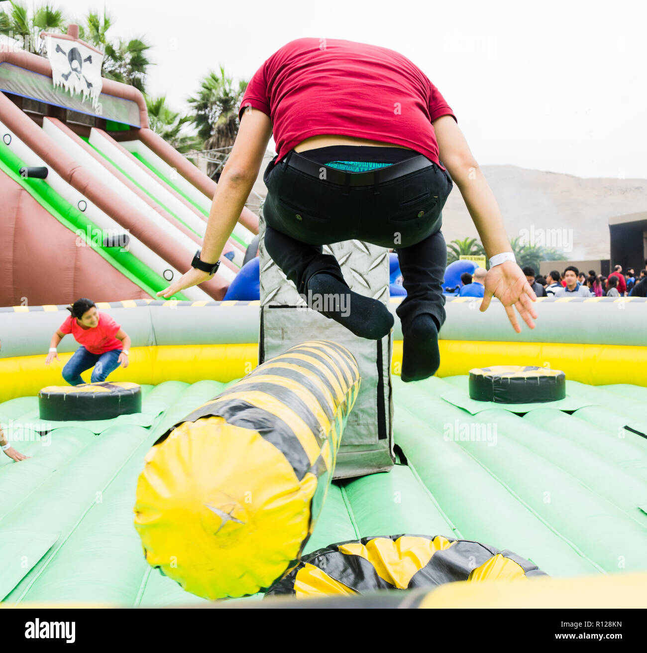 Young man jumping and dodging an obstacle in a game. - Stock Image