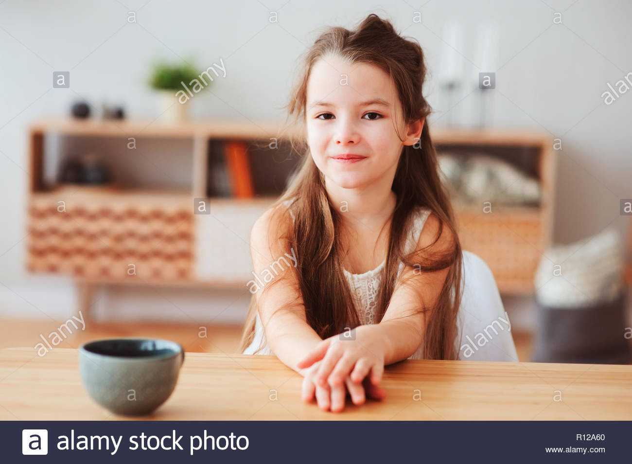 Portrait of a happy girl sitting at a table - Stock Image