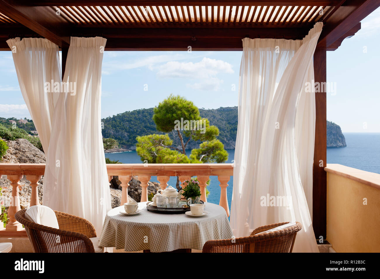 Table and chairs on balcony with curtains - Stock Image