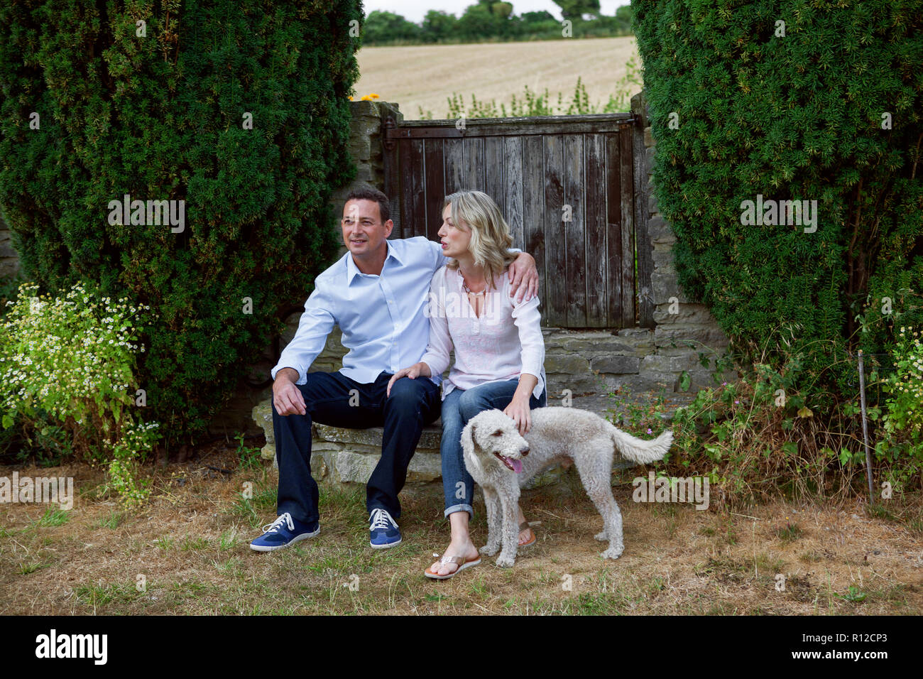 Romantic mature couple with dog sitting in garden Stock Photo