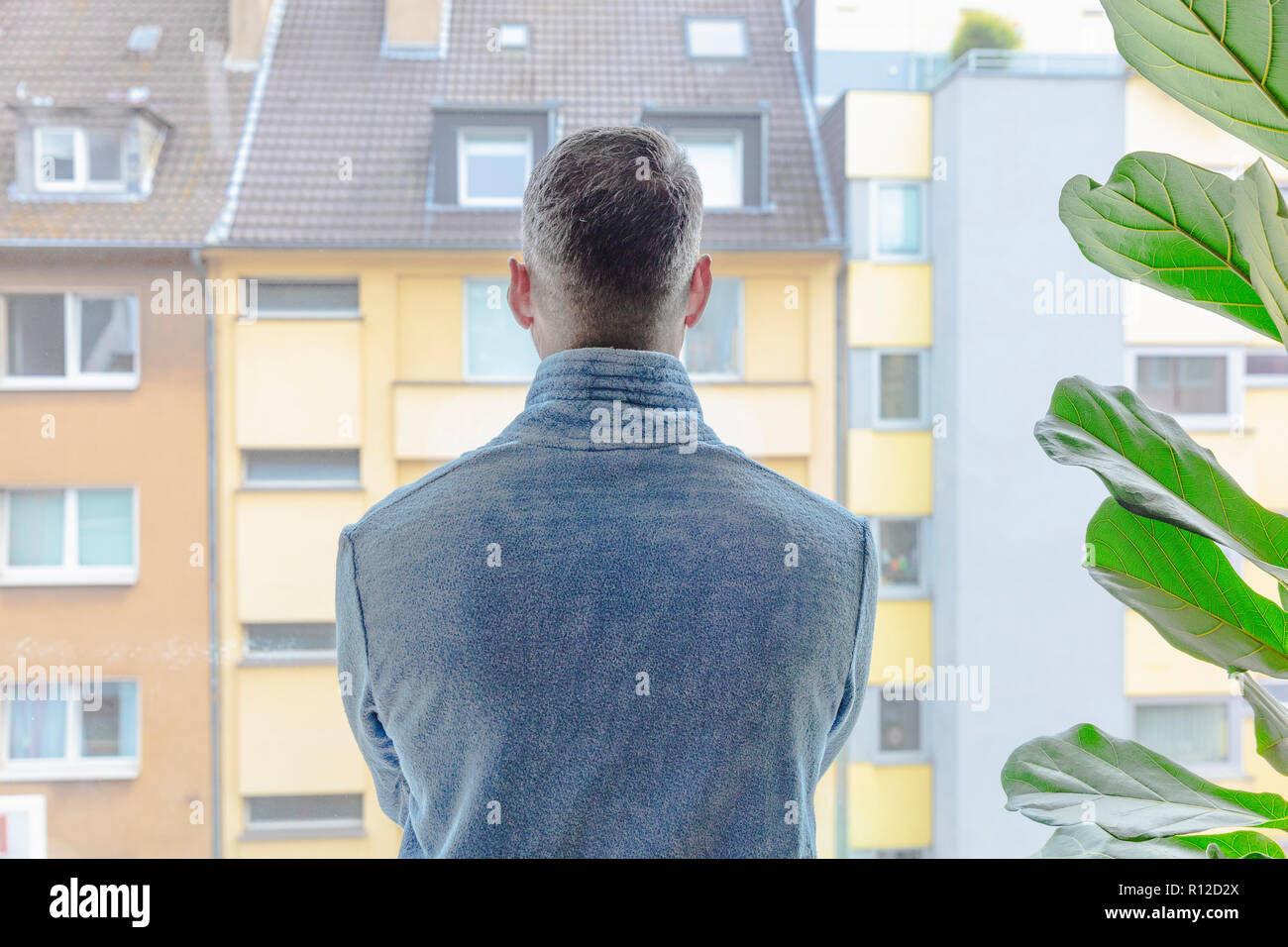 Man looking out of window at apartment block - Stock Image