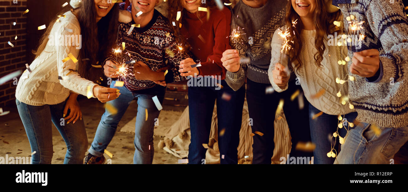 Christmas concept. Hands of friends with sparklers  at Christmas - Stock Image