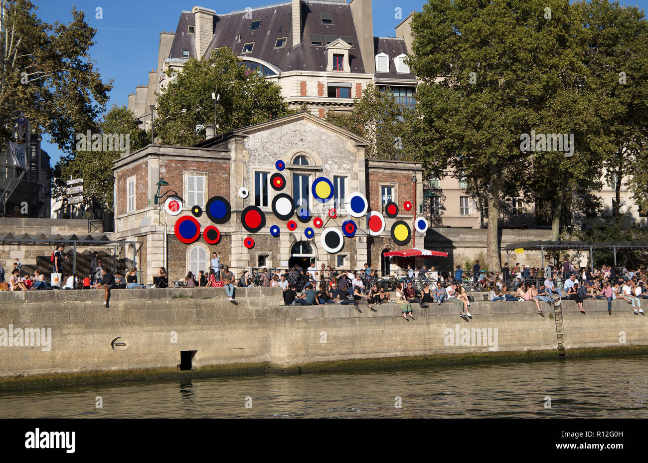 PARIS, FRANCE, SEPTEMBER 8, 2018 - People sit along the shores of the river Seine in a sunny day in Paris, France Stock Photo