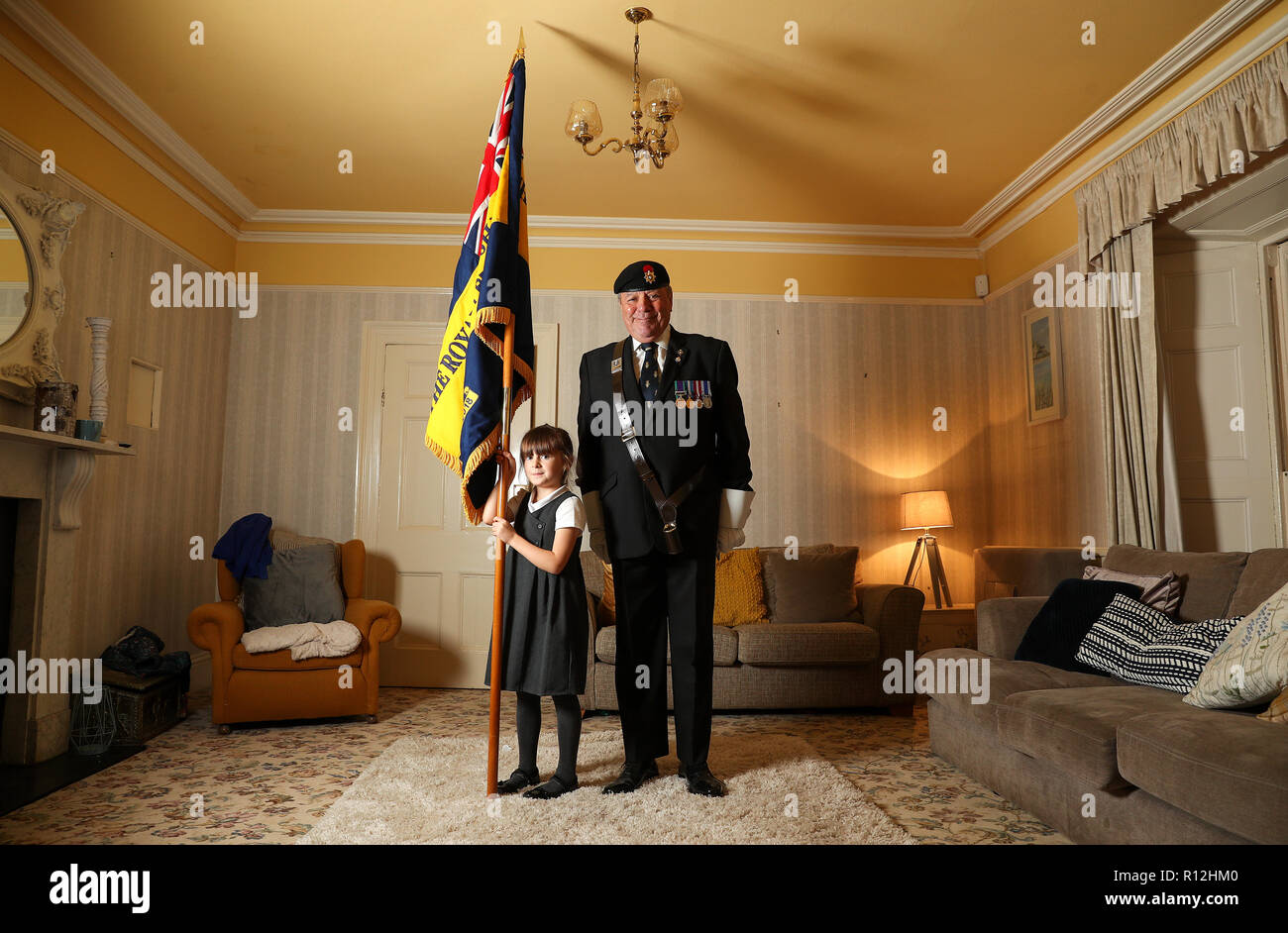 Mollie Stonelake, seven, holds a full-size standard from the Torpoint & District Branch of the Royal British Legion alongside branch chairman Colin Prideaux, in her family home in Torpoint, Cornwall. Mollie went on her first parade aged five and will carry a specially-made miniature standard in a service on Sunday in her home town of Torpoint in Cornwall. Stock Photo