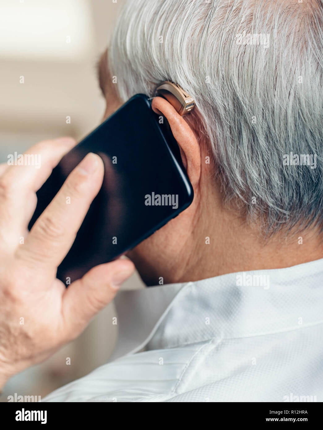 Senior man with hearing aid talking by phone - Stock Image