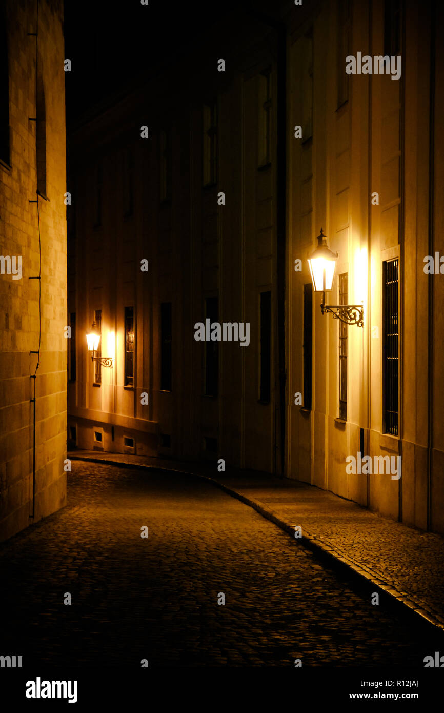 Old lanterns illuminating a dark alleyway medieval street at night in Prague, Czech Republic. Low key photo with brown yellow tones from the lanterns  - Stock Image