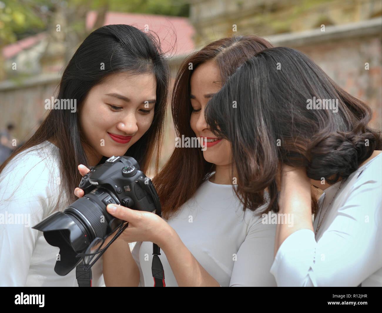 Three young Vietnamese women check photos on the screen of a Canon EOS 70D DSLR camera. Stock Photo