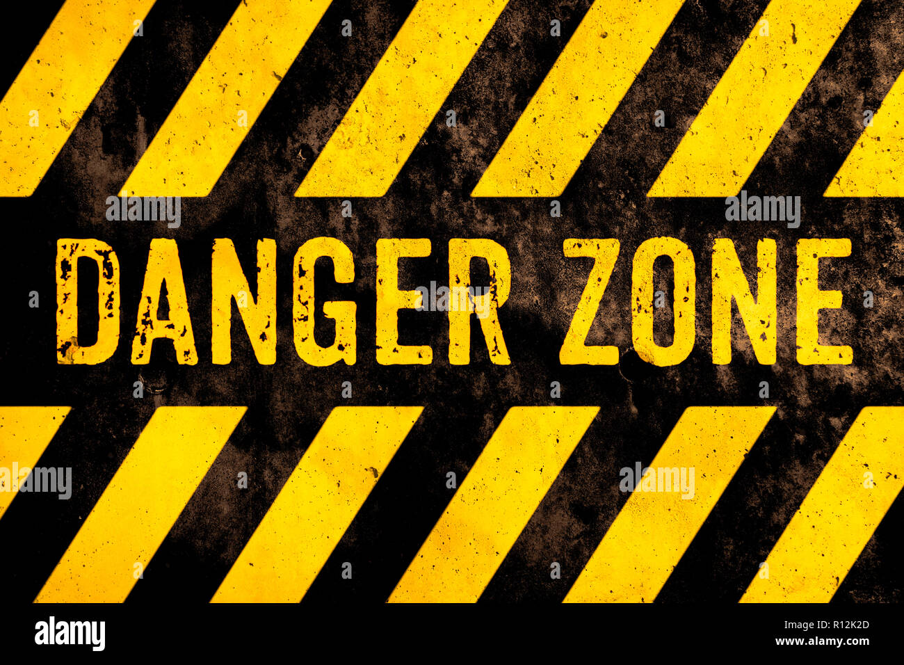 Danger zone warning sign text with yellow and black stripes painted over concrete wall surface facade cement texture background. Concept image for cau - Stock Image
