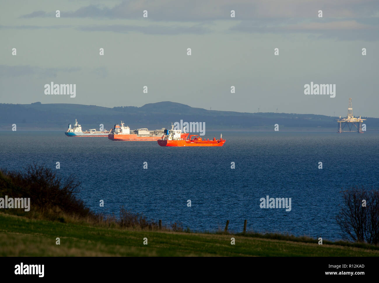 Commercial ships anchored off the east coast of Scotland in the Firth of Forth. - Stock Image