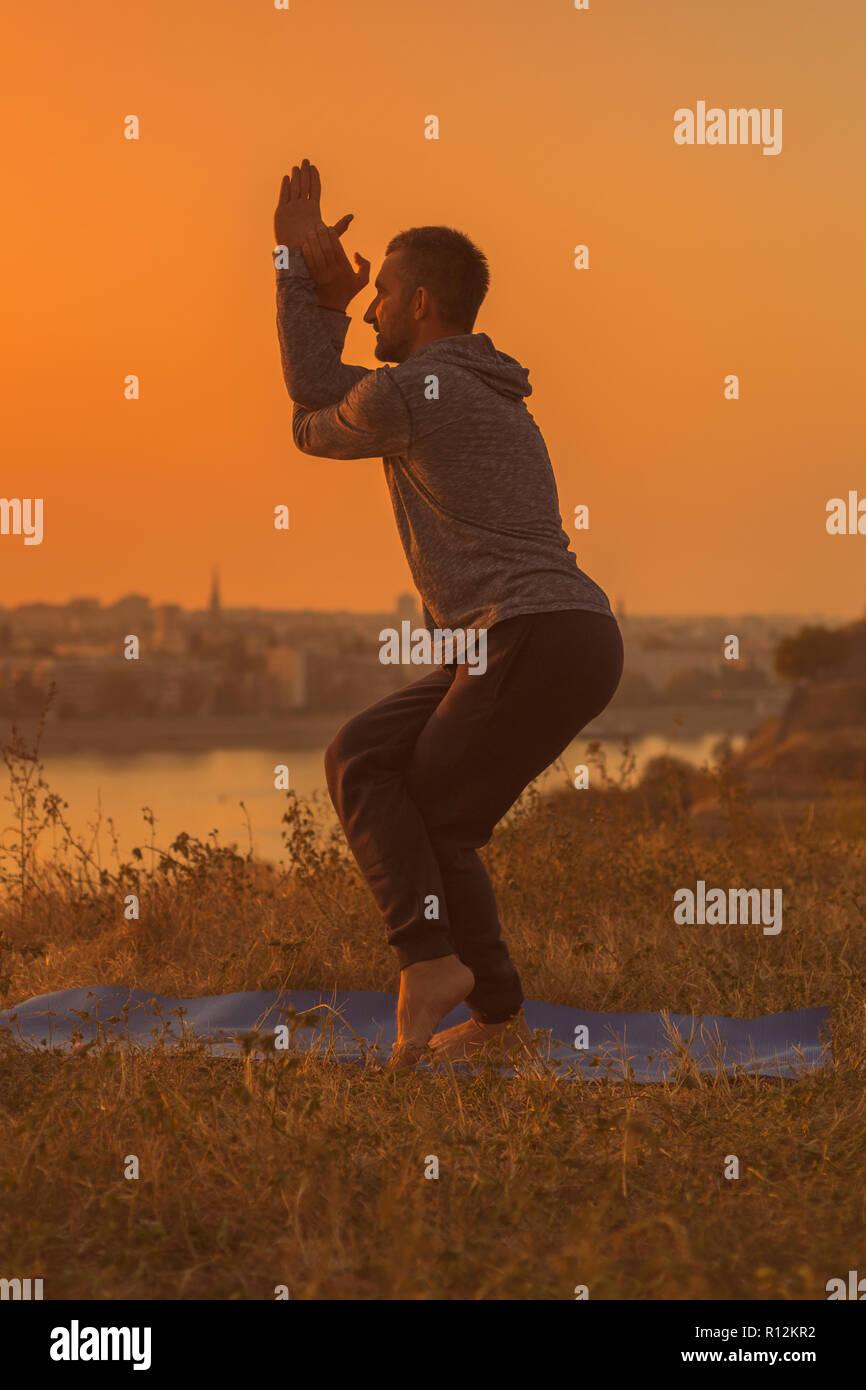 Man doing yoga on sunset with city view,Garudasana/Eagle Pose.Toned image. - Stock Image
