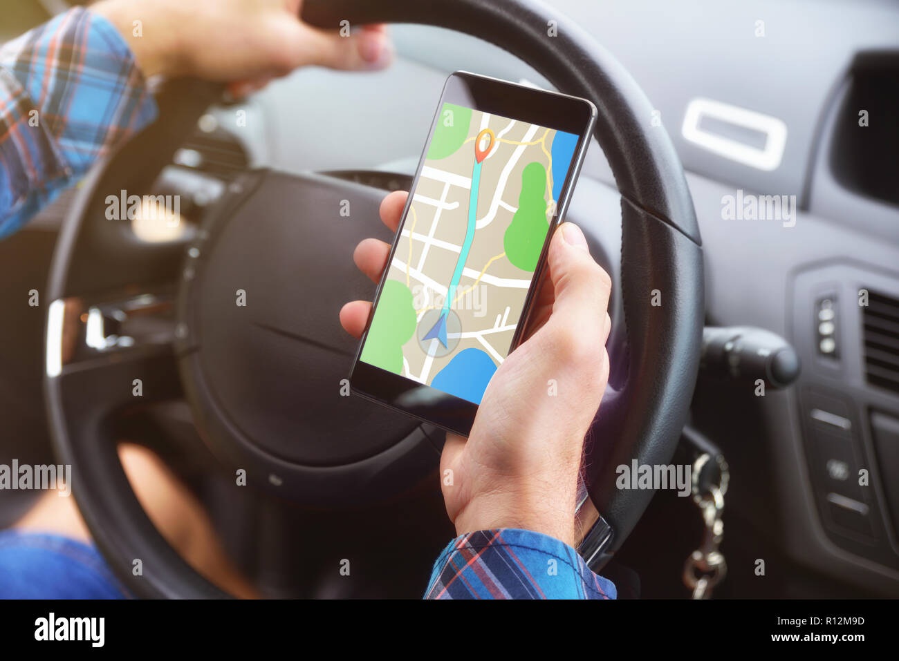 Man consulting a route on a cell phone with an application to reach his destination in a car. Stock Photo