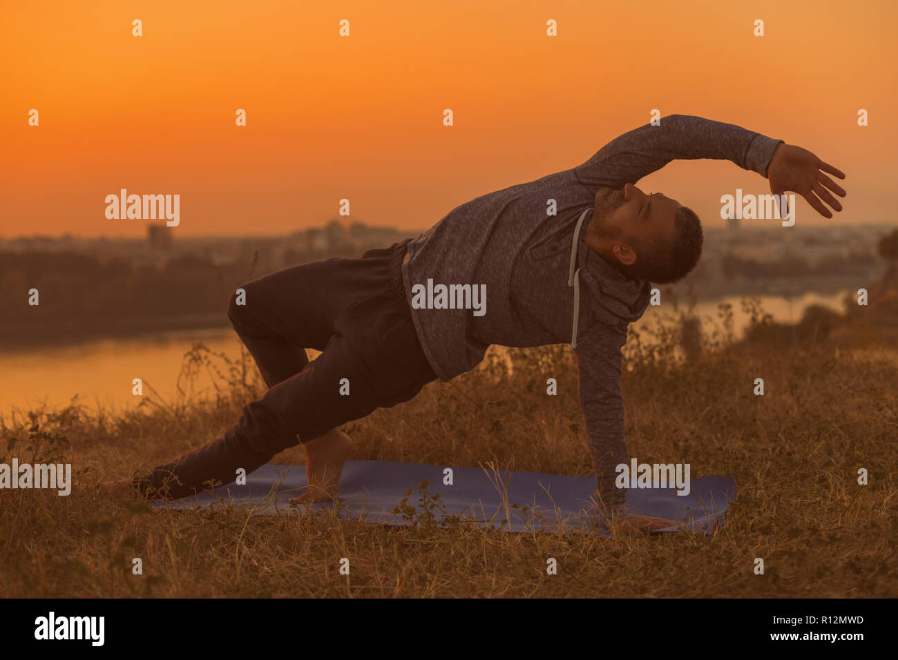 Man doing yoga on sunset with city view,variation of Side Plank Pose/Vasisthasana. - Stock Image