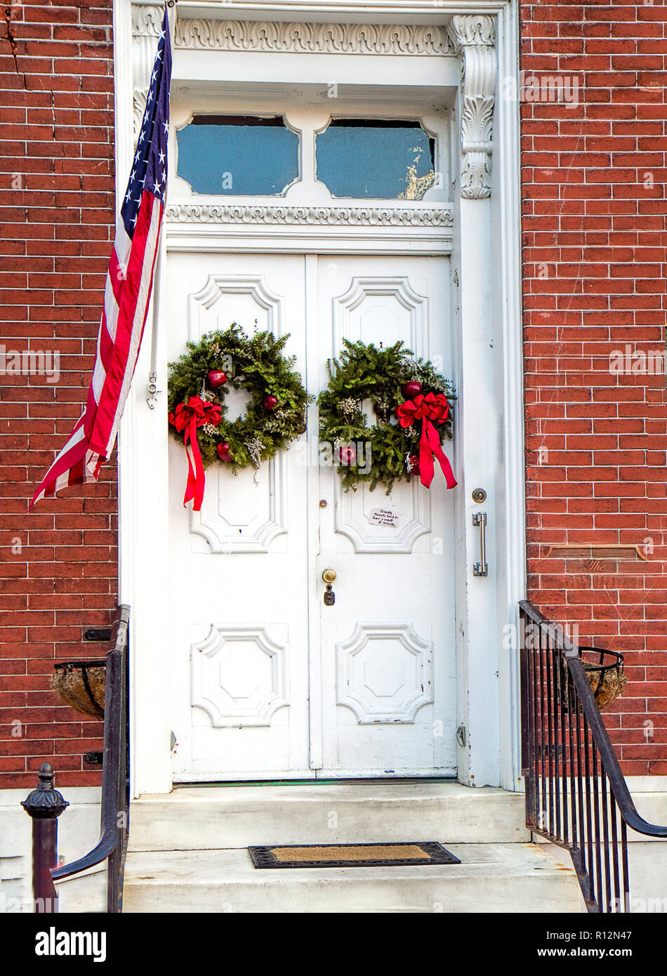 Exterior doors in historic town decorated for the Christmas holidays giving a feeling of yesteryear.  Closeup of doors only. Stock Photo