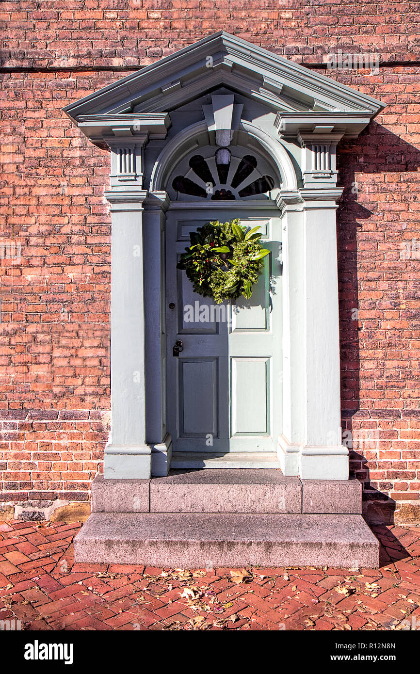 Exterior doors in historic town decorated for the Christmas holidays giving a feeling of yesteryear.  Closeup of doors only. - Stock Image