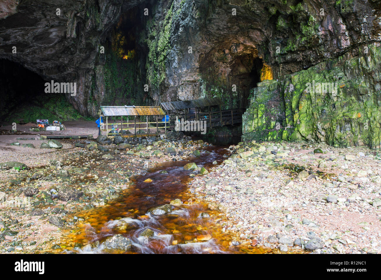 Smoo Cave in Durness, Sutherland, UK, the UK's largest sea cave, with a heavily peat stained river flowing through it. - Stock Image