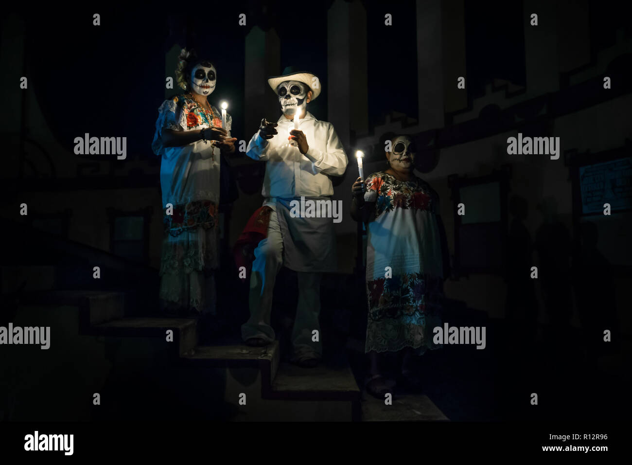 Merida, Cementerio General, Mexico - 31 October 2018: Customed man with candles and pointing and two woman dressed as Catrinas with skull make-up posi - Stock Image