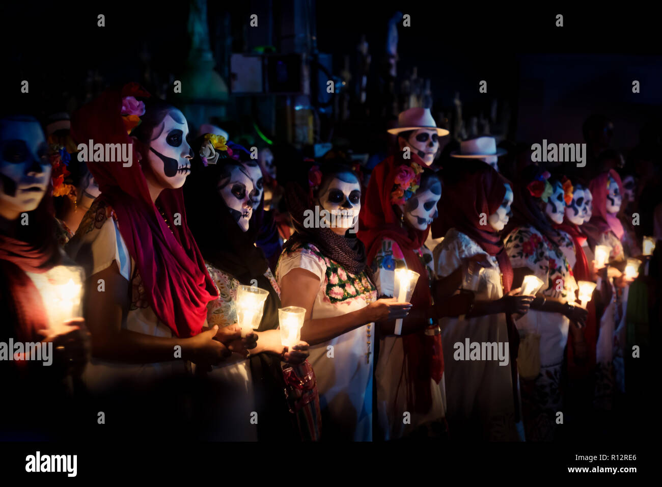 Merida, Cementerio General, Mexico - 31 October 2018: Line of customed women dressed as Catrinas with skull make-up and candles at the event for dia d - Stock Image