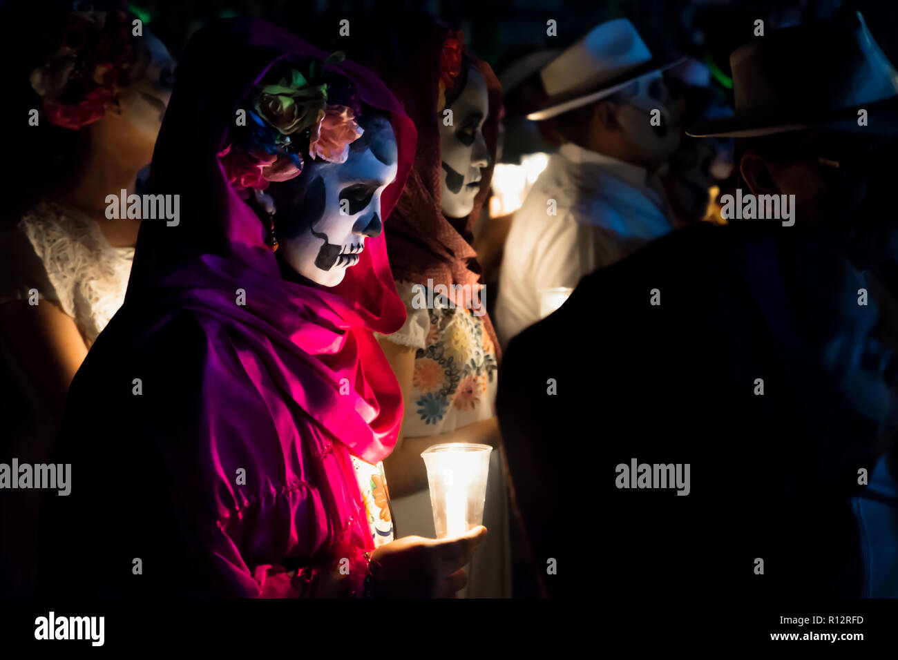 Merida, Cementerio General, Mexico - 31 October 2018: Close up of customed women dressed as Catrinas with skull make-up holding candles at the process - Stock Image