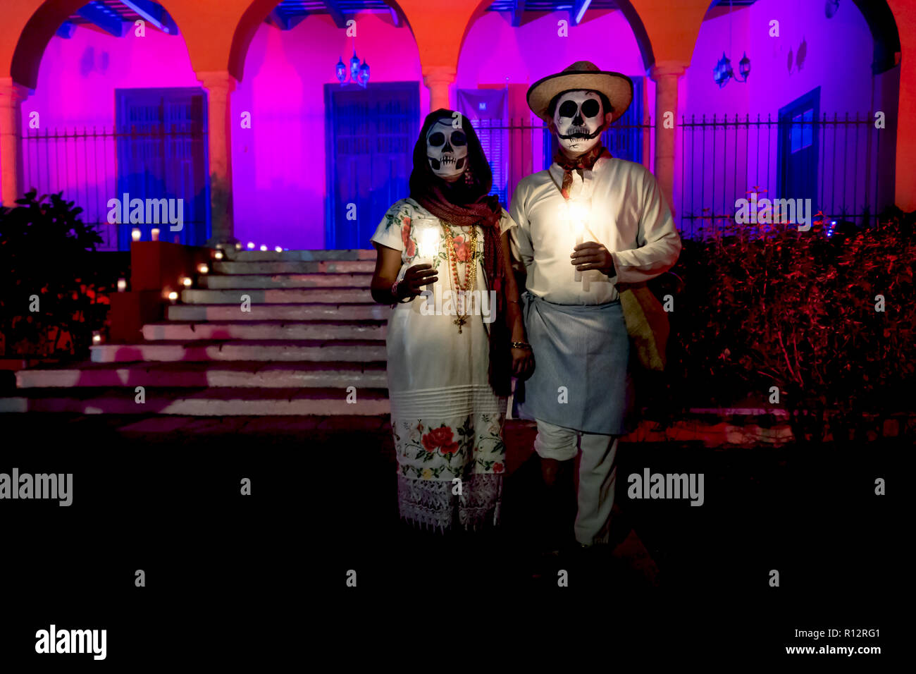 Merida, Cementerio General, Mexico - 31 October 2018: Customed man and woman with with mexican traditional white clothes and skull make-up in front of - Stock Image