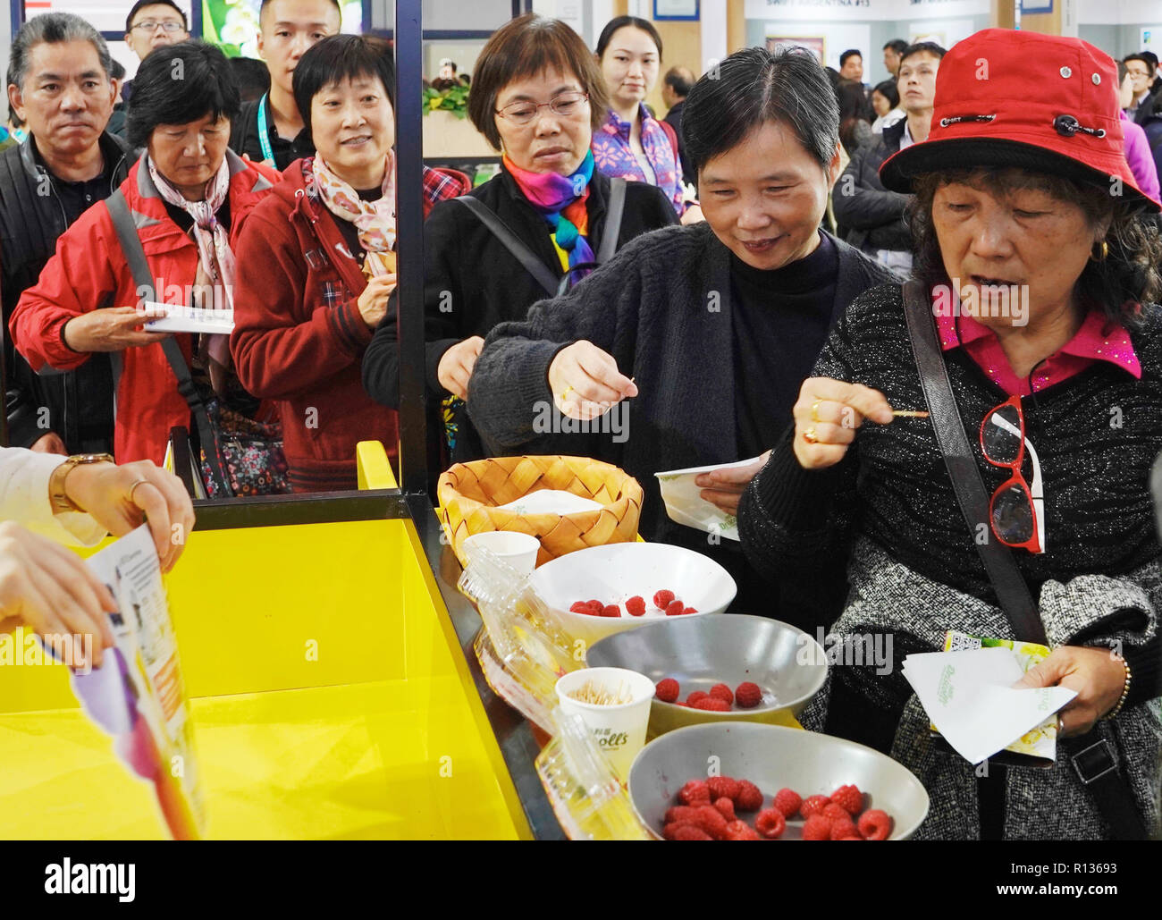 Shanghai, China. 9th Nov, 2018. Visitors line up to taste berry samplings during the first China International Import Expo (CIIE) in Shanghai, east China, Nov. 9, 2018. The CIIE is opened to group visitors from Nov. 9 to Nov. 10. Credit: Bi Xiaoyang/Xinhua/Alamy Live News - Stock Image