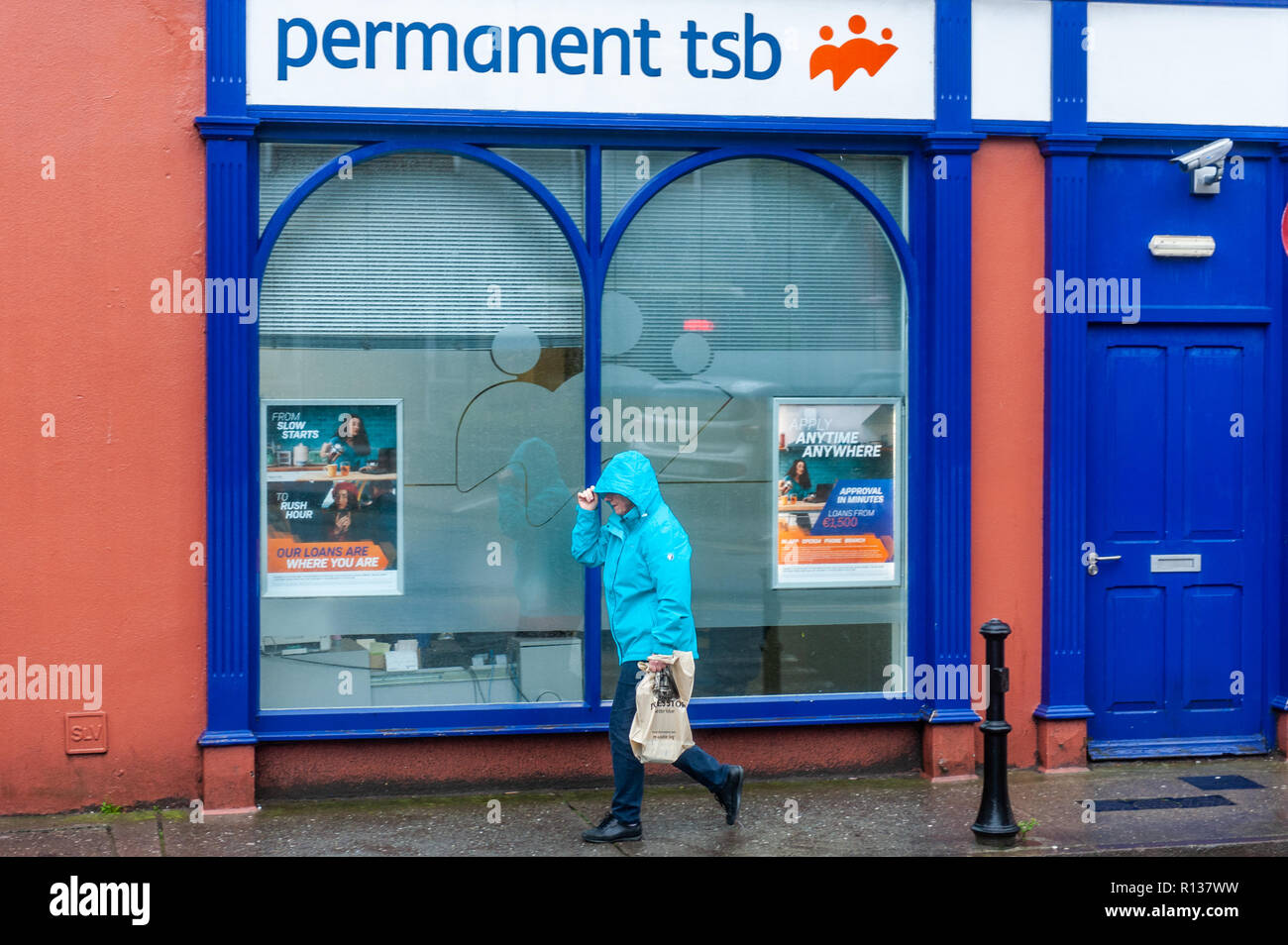 Skibbereen, West Cork, Ireland. 9th Nov, 2018. A shopper braves the elements in Skibbereen.  This afternoon will see a continuation of strong winds, which will reach gale force on the coasts. Highs today of 9 to 13°C. Credit: Andy Gibson/Alamy Live News. - Stock Image