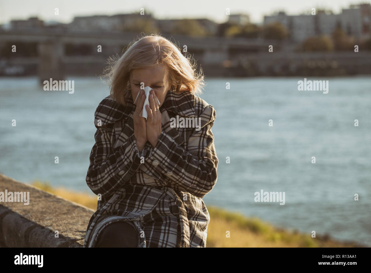 Senior woman blowing nose while sitting by the river. - Stock Image