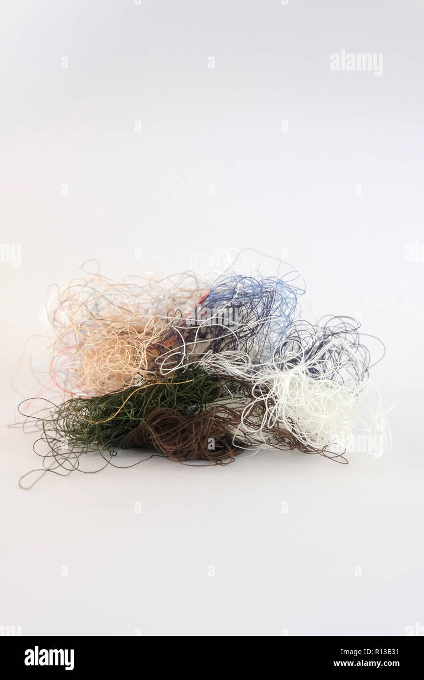 Tangled mess of sewing thread - Stock Image