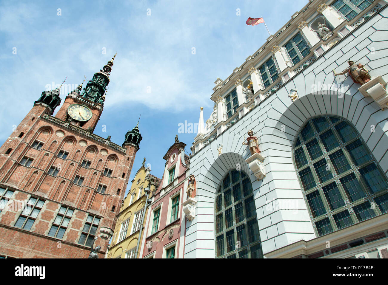The view of historic town hall and restored 14th century Artus Court, merchant's meeting place in Gdansk old town (Poland). - Stock Image
