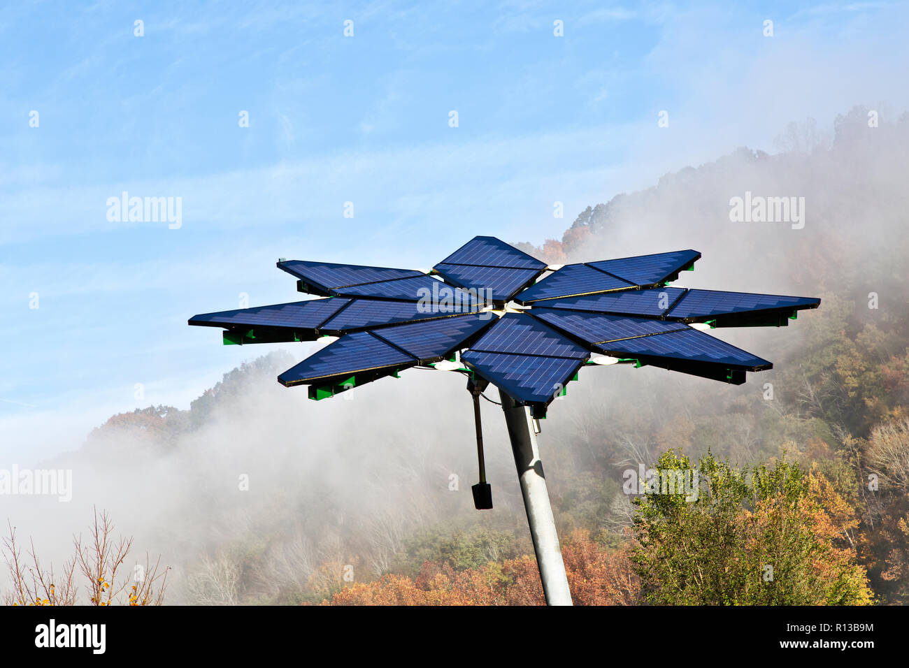 Solar array identified as a  'Solar Photovoltaic Flair',  facilitates electric vehicle charging station, dissipating morning fog. - Stock Image