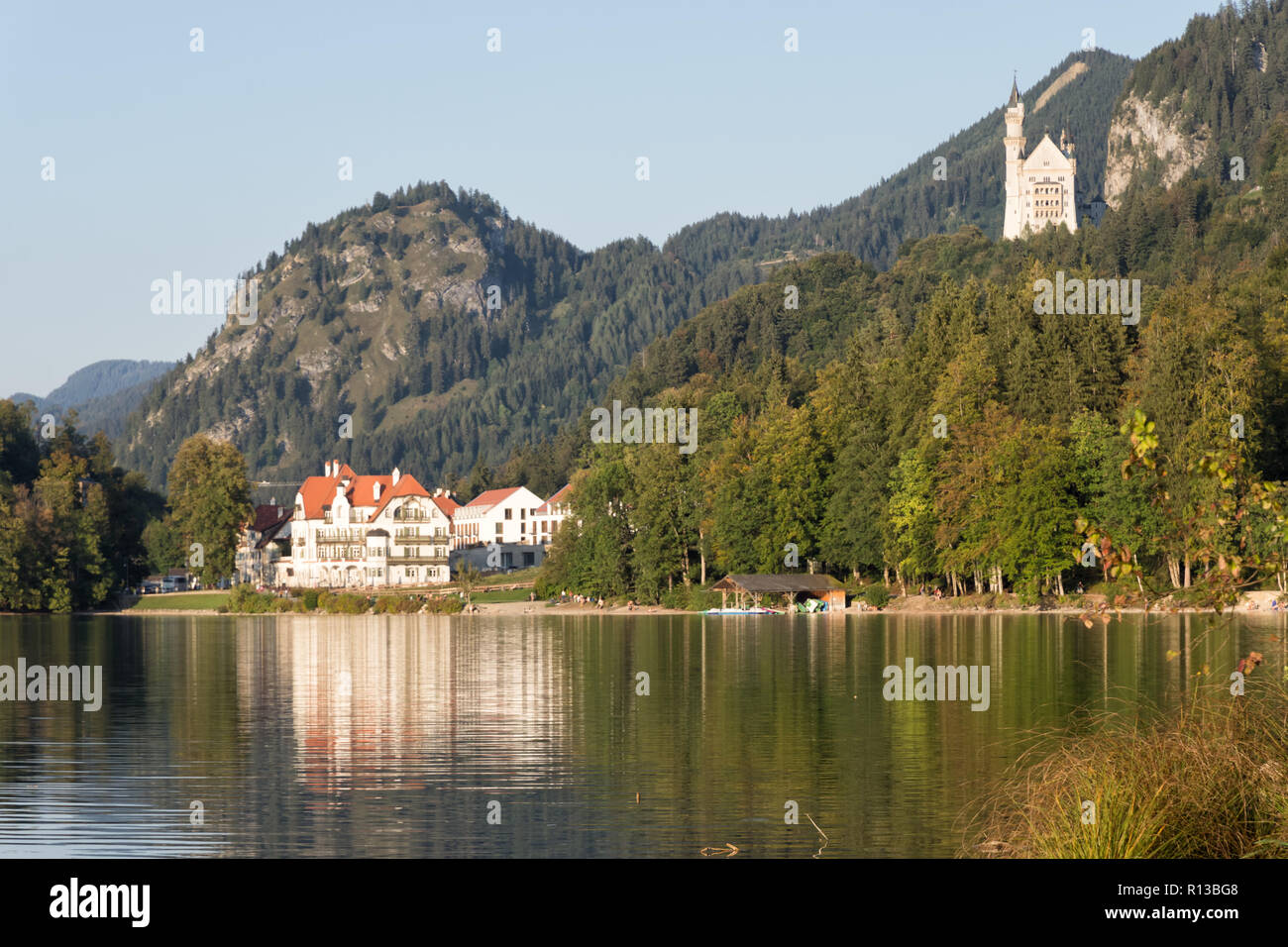 Lake Alpsee, Füssen, with Neuschwanstein, Restaurant Alpenrose am See and next to the Restaurant the newly built hotel on a warm sunny evening - Stock Image