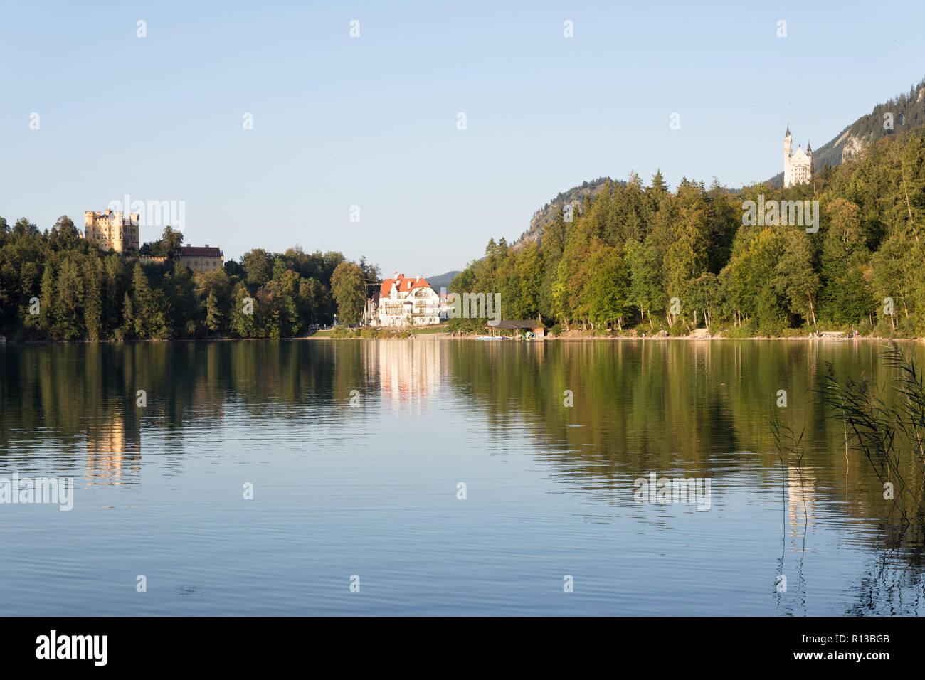 Lake Alpsee, Füssen, with Hohenschwangau, Neuschwanstein, Restaurant Alpenrose am See on a warm sunny evening in late September. Schwangau, Bavaria - Stock Image