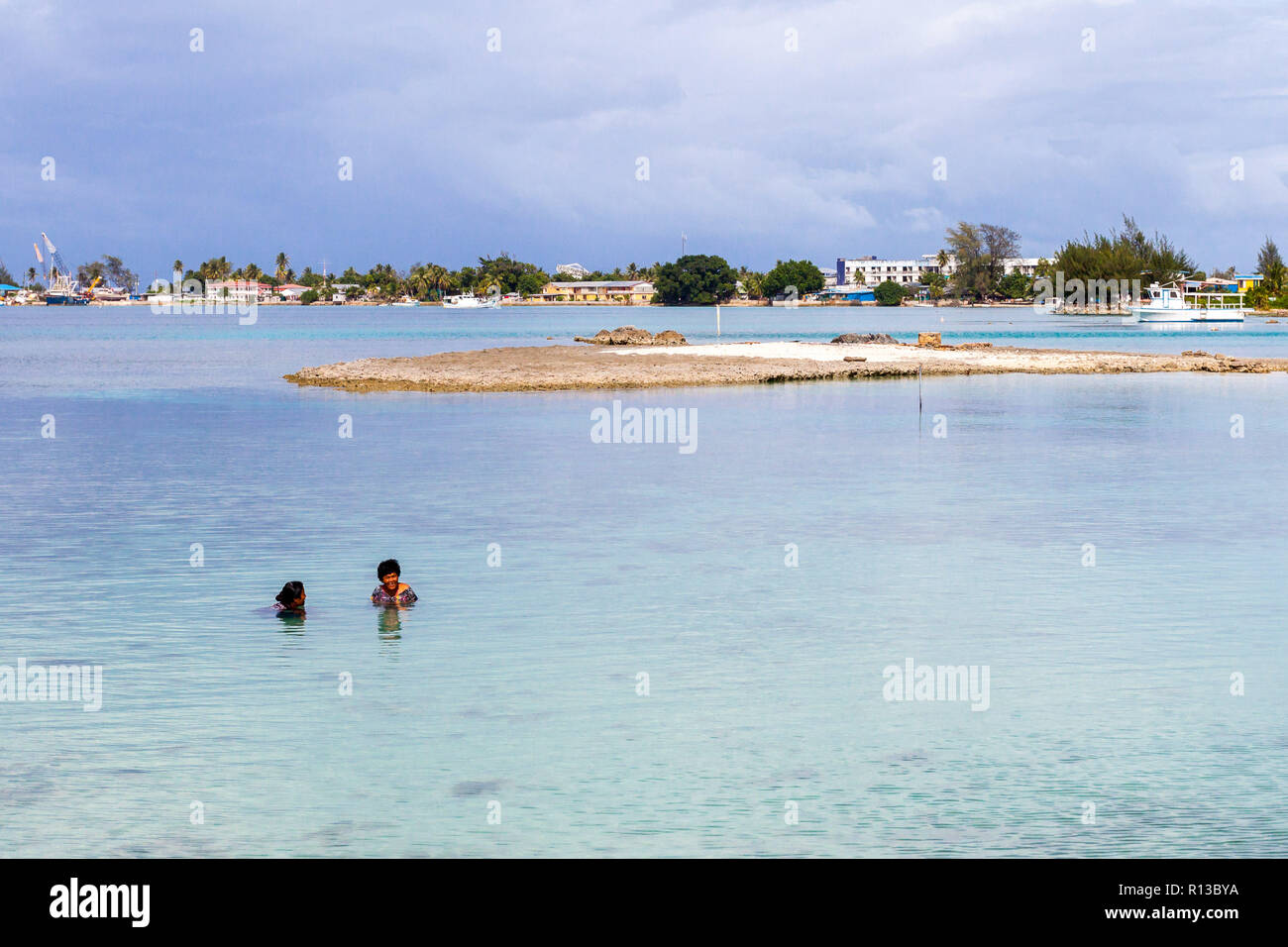 Majuro atoll, Marshall islands - Jan 4 2012: Two middle aged local Micronesian women in closing enjoying swimming in rocky blue turquoise lagoon. - Stock Image