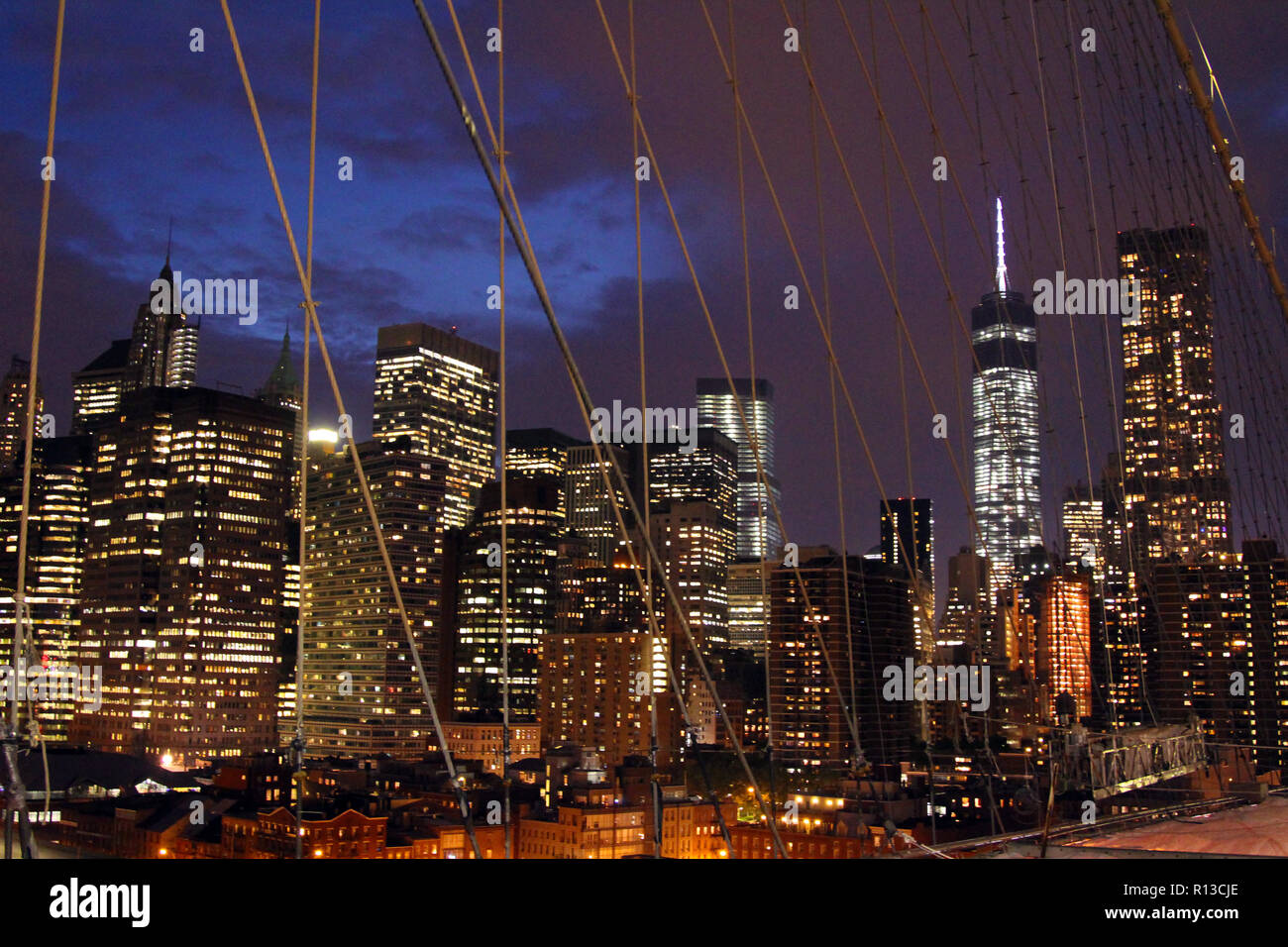 View of lower Manhattan through cable trusses of the Brooklyn Bridge, New York, NY - Stock Image