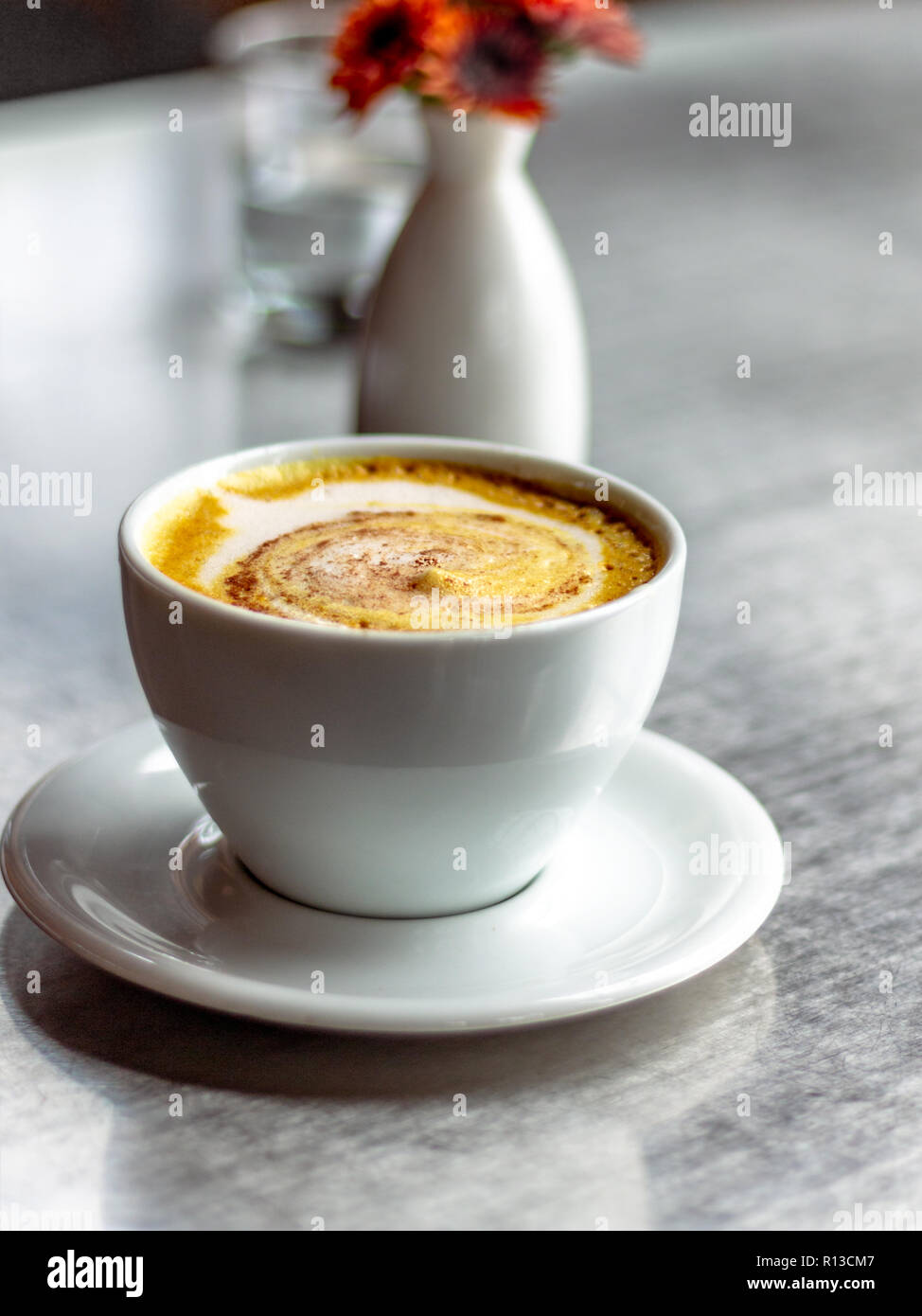 Casual Coffee shop. Latte art. Foaming latte. Water jug in clear glass. orange flowers in a white oval white vase. - Stock Image